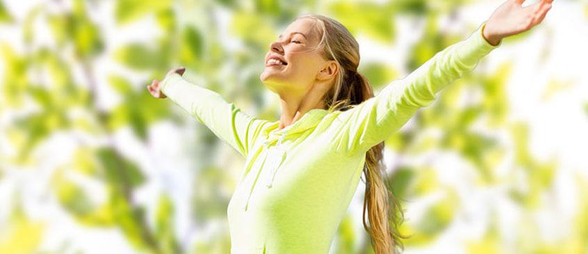 Frau in Sportoutfit genießt draußen die Sonne