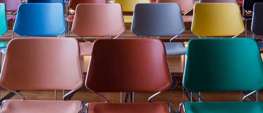 Bunte leere Stühle in einem Hörsaal