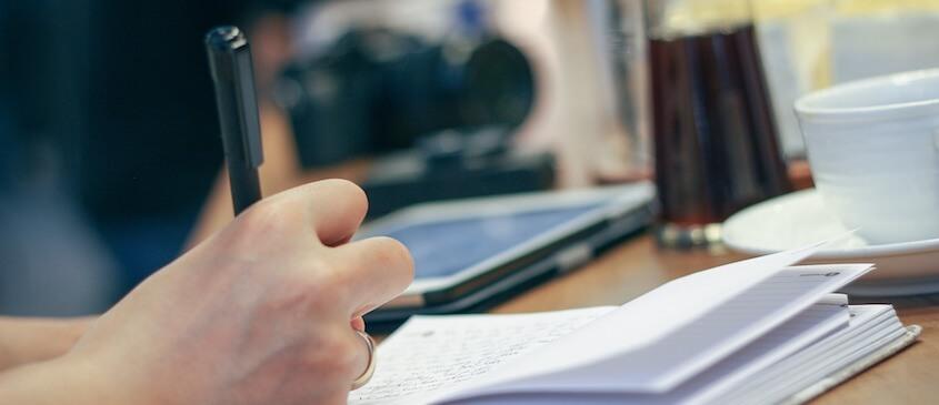 Frau schreibt in ein Notizbuch